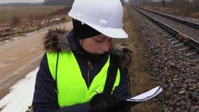 Ingeniero ferroviario de sexo femenino que escribe y que piensa cerca de ferrocarril almacen de metraje de vídeo
