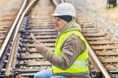 Ingeniero ferroviario en los carriles con la tableta Imágenes de archivo libres de regalías