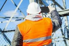 Ingeniero filmado con la tableta en el aire libre cerca de las estructuras del metal Imagen de archivo