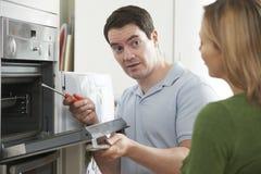 Ingeniero Giving Woman Advice en la reparación de la cocina Imágenes de archivo libres de regalías