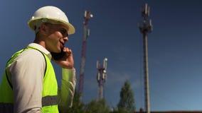 Ingeniero In Helmet Talking en el teléfono con el director almacen de metraje de vídeo