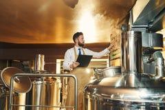 Ingeniero hermoso de la cervecería que examina el proceso de la elaboración de la cerveza fotografía de archivo