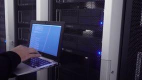 Ingeniero Holds Laptop del centro de datos y pruebas la estabilidad del sistema La imagen tiene un ruido leve