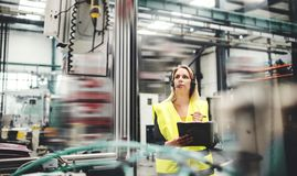 Ingeniero industrial de la mujer con las auriculares en una fábrica, trabajando Copie el espacio imagen de archivo