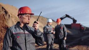 Ingeniero industrial de sexo masculino que habla usando el Walkietalkie en el tiro medio del emplazamiento de la obra almacen de video