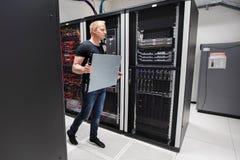 Ingeniero informático Carrying Blade Server mientras que camina en Datacen Imágenes de archivo libres de regalías