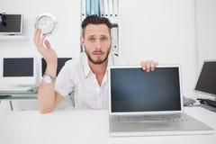 Ingeniero informático confuso que mira la cámara con el ordenador portátil Fotografía de archivo