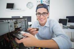 Ingeniero informático sonriente que trabaja en la consola quebrada con destornillador Imagenes de archivo