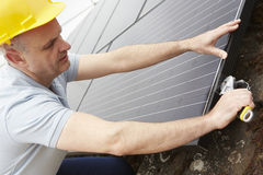 Ingeniero Installing Solar Panels en el tejado de la casa Foto de archivo libre de regalías