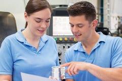 Ingeniero Instructing Female Apprentice en el uso de la máquina del CNC imagen de archivo
