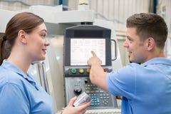 Ingeniero Instructing Female Apprentice en el uso de la máquina del CNC imagenes de archivo