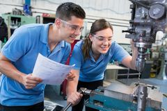 Ingeniero Instructing Female Apprentice en el uso del taladro imagen de archivo libre de regalías