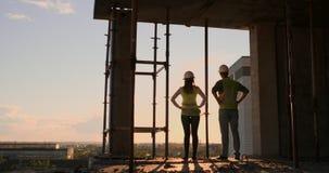 Ingeniero jefe dos con un dibujo a disposición que mira el emplazamiento de la obra Visi?n desde la parte posterior Ingeniero jef metrajes