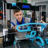 Ingeniero joven del diseñador usando una impresora 3D en laboratorio imagen de archivo libre de regalías
