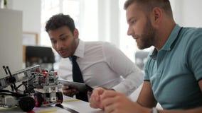 Ingeniero joven que muestra a colega su nuevo robot