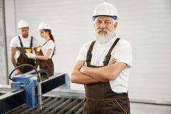 Ingeniero mayor que presenta en fábrica metalúrgica imagenes de archivo