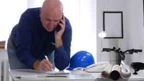 Ingeniero ocupado en charla de la oficina a las notas del móvil y de la toma en orden del día metrajes