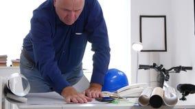 Ingeniero ocupado Examine una calma de pensamiento del plan de la construcción y cálculos de la fabricación almacen de video