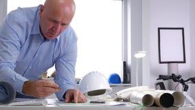 Ingeniero ocupado Open y estudiar un plan constructivo en oficina de la arquitectura almacen de video