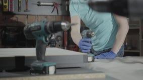 Ingeniero principal joven del retrato centrado en la perforación de un agujero con la herramienta en el fondo de un pequeño talle almacen de metraje de vídeo