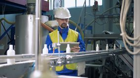 Ingeniero profesional que comprueba el trabajo del transportador automatizado, máquina de la fábrica metrajes