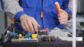Ingeniero que atornilla las conexiones en caja del fusible Primer 4K almacen de video