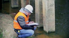 Ingeniero que comprueba la documentación cerca de las ayudas del puente metrajes