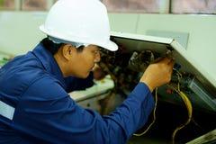 Ingeniero que comprueba y que repara el sistema eléctrico imagenes de archivo