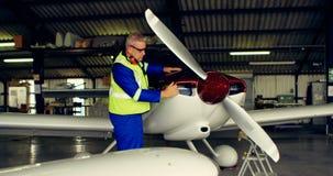 Ingeniero que fija un avión en el hangar 4k almacen de metraje de vídeo