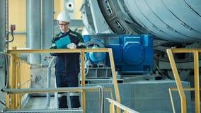 Ingeniero que firma un documento en fábrica industrial metrajes