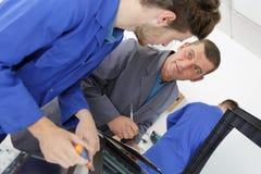 Ingeniero que habla con el aprendiz sobre la máquina imagen de archivo