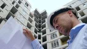 Ingeniero que lleva a cabo planes y que examina la construcción almacen de video