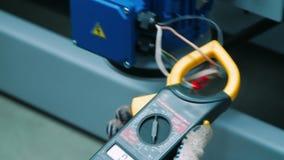 Ingeniero que mide parámetros técnicos de la máquina industrial con el probador metrajes