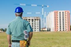 Ingeniero que mira el edificio en la construcción Imagenes de archivo