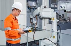 Ingeniero que programa el CNC robótico automático de la máquina-herramienta de la mano fotografía de archivo