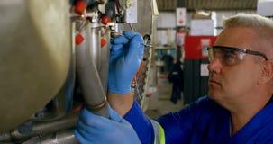 Ingeniero que repara el motor de avión en el hangar 4k almacen de metraje de vídeo