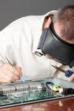 Ingeniero que repara la tarjeta de circuitos Fotos de archivo libres de regalías