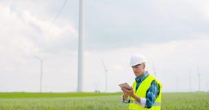 Ingeniero que usa la tableta digital al hacer la inspección de la turbina de viento metrajes