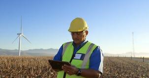 Ingeniero que usa la tableta digital en el parque eólico 4k almacen de video