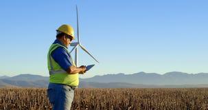 Ingeniero que usa la tableta digital en el parque eólico 4k almacen de metraje de vídeo