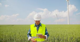 Ingeniero que usa la tableta digital en granja de la turbina de viento almacen de metraje de vídeo