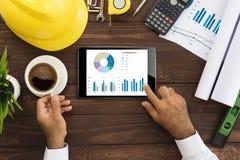 Ingeniero que usa la tableta que comprueba el gráfico de negocio en la tabla imagen de archivo libre de regalías