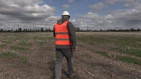 Ingeniero que usa la tableta y caminando en el campo cerca de fábrica almacen de video