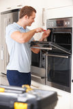 Ingeniero Reapiring Domestic Oven In Kitchen Foto de archivo