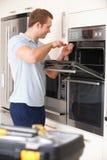 Ingeniero Reapiring Domestic Oven In Kitchen Foto de archivo
