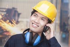 Ingeniero sonriente joven en el teléfono que lleva un casco de protección, en sitio Foto de archivo libre de regalías