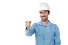 Ingeniero sonriente que lleva a cabo llave imagen de archivo libre de regalías