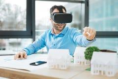 Ingeniero sonriente que usa las auriculares de VR mientras que diseña la construcción imagen de archivo libre de regalías