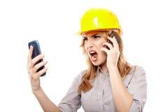 Ingeniero subrayado de la mujer que usa dos teléfonos celulares y gritando Imagenes de archivo