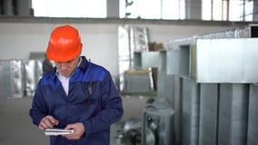 Ingeniero, supervisor de la construcción, constructor, worket usando el ordenador portátil en un emplazamiento de la obra dentro  almacen de metraje de vídeo